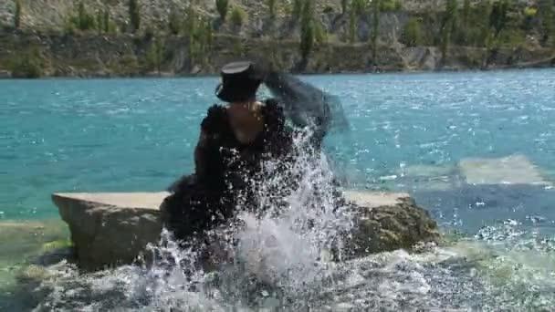 Žena v černém, stříkající vodě v rybníku