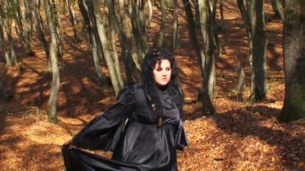 Dark Haired Woman In Black Walking In Autumn Forest