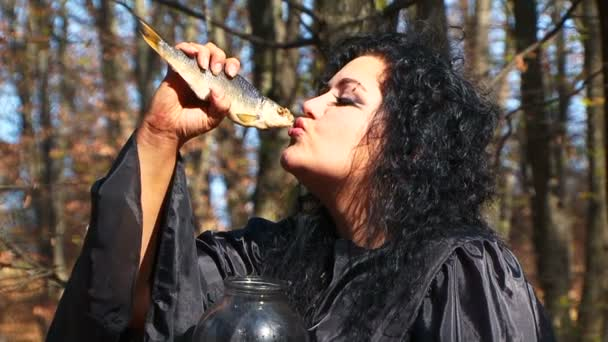 Dark Haired Woman In Black With Dried Fish Posing In Autumn Forest