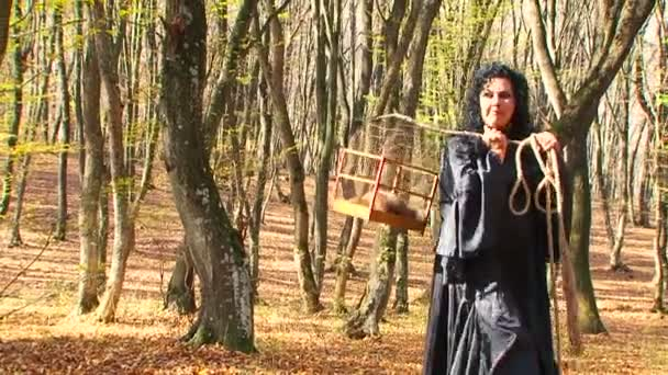 Woman In Black Walking In Autumn Forest With Cage