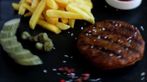 Grilovaný hamburger s hranolky a omáčkou z nakládaných okurek
