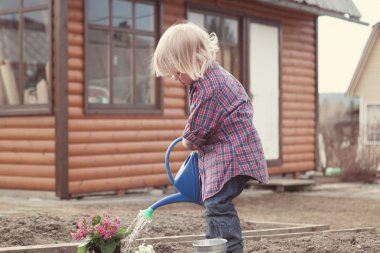 Little girl planting and watering flowers in garden