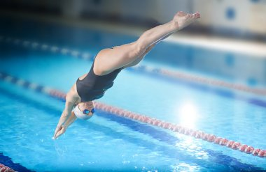 Female swimmer jumping into swimming pool.