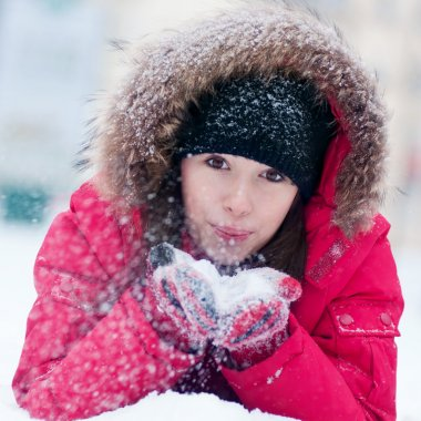 Young woman plays with a snow