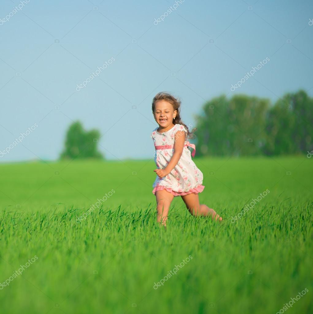 Girl running at green wheat field