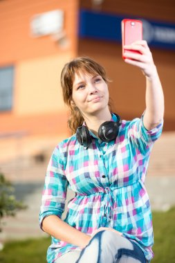 Happy young wpman taking pictures of herself through cell phone. Selfie.