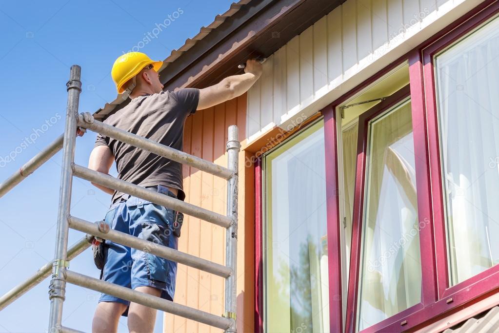 Travailleur de la construction sur la peinture de fa ade de maison en bois d chafaudage photo - La maison de la peinture ...