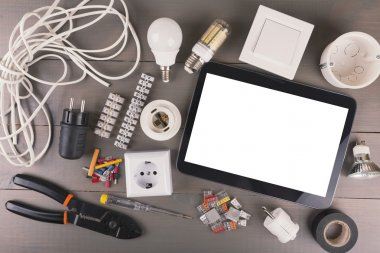 blank digital tablet with electrical tools and equipment on wood