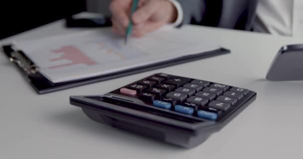 účetní pracující na sestavě v kanceláři pomocí kalkulačky digitální tablet a grafy