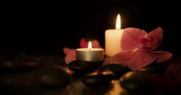 svíčky s lázeňskými kameny a orchideje květiny na tmavém pozadí. aromaterapie, kosmetická léčba a wellness koncept