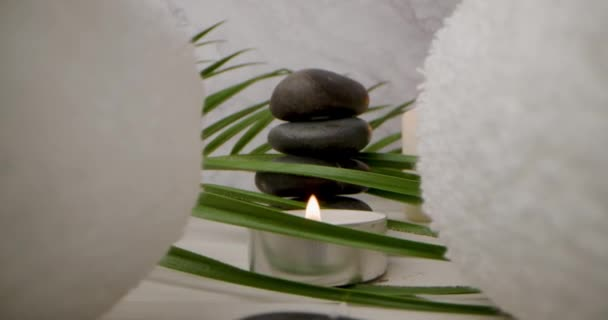 lázně a wellness - klouzání po bílých ručnících přes masážní kameny