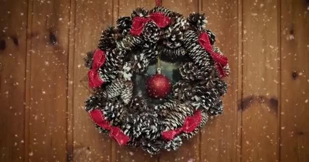 An der Haustür hängt ein Adventskranz. Hausdekoration. Draußen schneit