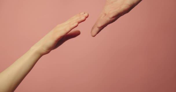 Helfende Hand - Unterstützung, Hilfe und Wohltätigkeitskonzept. Hände, die auf rosa Hintergrund zusammenreichen
