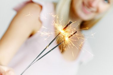 smiling woman holding sparklers in her hand