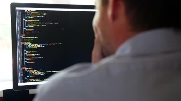 programátor zezadu a programového kódu na monitoru počítače