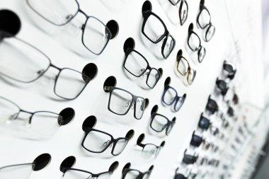 optical store, wall of many fashionable eyeglasses