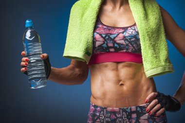 Muscular woman holding a bottle of water stock vector