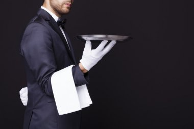 Waiter holding an empty silver tray