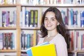 studentka drží knihy v knihovně
