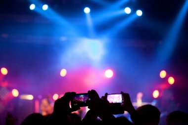 People at rock concert taking photos with cell phone stock vector