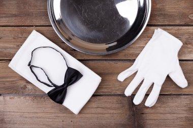 waiter tray, bow tie, gloves and a napkin