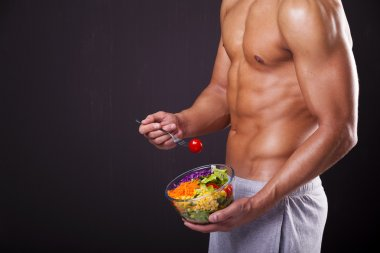 Fit man holding a bowl of fresh salad on grunge background stock vector