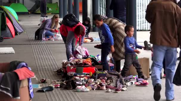 BUDAPEST, HUNGARY - AUTUMN 2015: Immigrants and refugees dismantled clothes and warm clothes at the railway station in Budapest. Shot in 4K, UHD