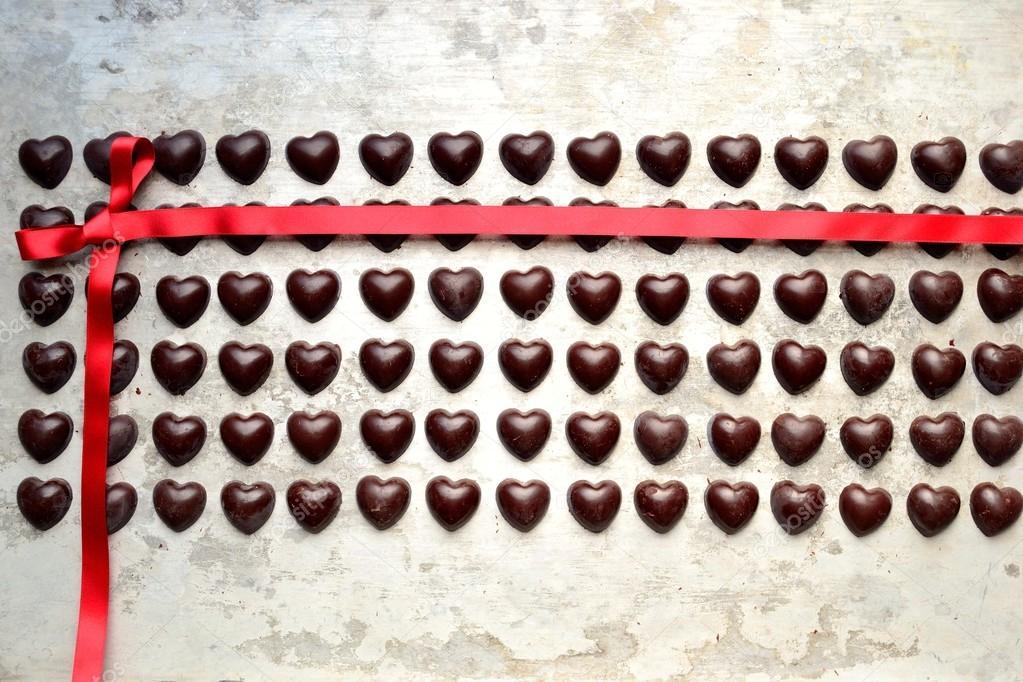 Herzförmige Pralinen mit roter Schleife auf der silbernen Rückseite ...