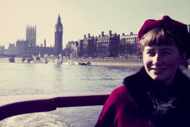 original vintage colour slide from 1960s, young woman on a tourist boat in London, houses of parliment in background.