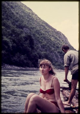 original vintage colour slide from 1960s, woman enjoying a raft trip down a river.