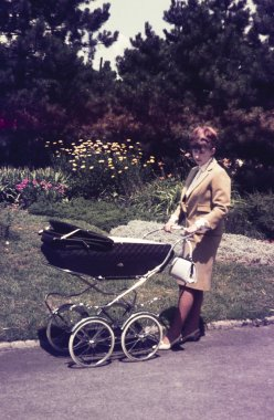 original vintage colour slide from 1960s, young mother walking her baby.