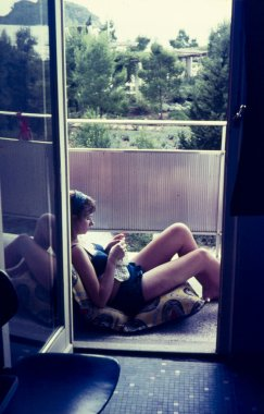 original vintage  colour slide from 1960s, young woman relaxing reading a book on vacation.