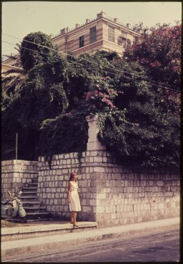 original vintage colour slide from 1960s, woman standing in street with vintage moped in background.