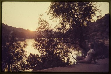 original vintage colour slide from 1960s, young woman enjoys sunset by a lake.