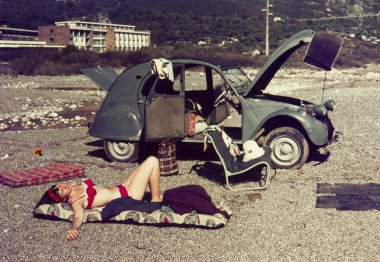 original vintage colour slide from 1960s, young woman laying on a beach with her old car.