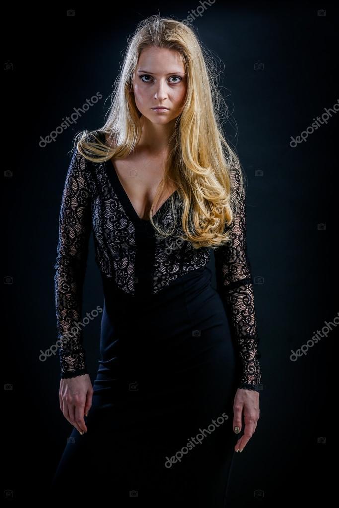 blonde Mädchen auf einem schwarzen Hintergrund in einem dunklen ...