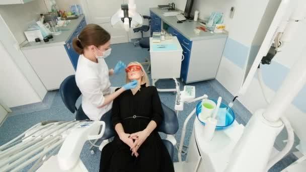 Zubař držící zubní nástroje v ústech klientky. Zubař drží sondu v jedné ruce a náustek v druhé. Doktor zkontroluje stav zubů. skříňka