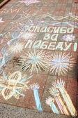 Zeichnung mit Kreide auf dem Bürgersteig mit Text in Russisch Thanks For Victory