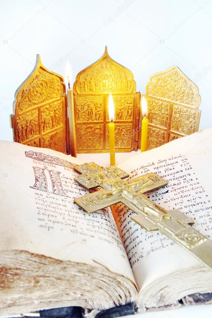 Orthodox Christian still life with an open ancient Bible and metal cross on light background