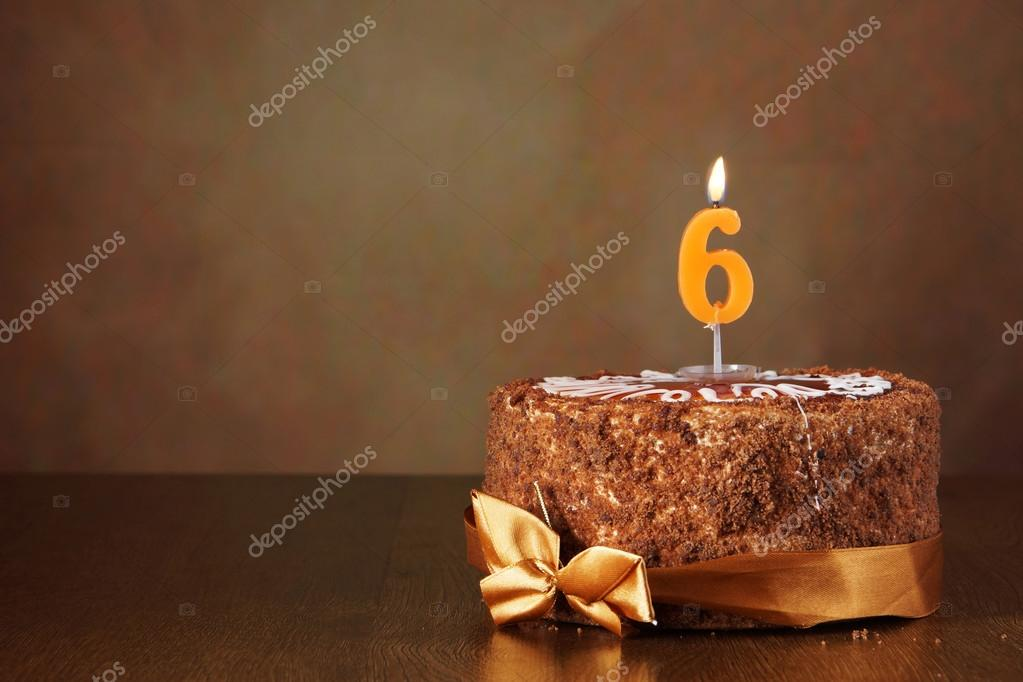 Birthday chocolate cake with burning candle as a number six on b