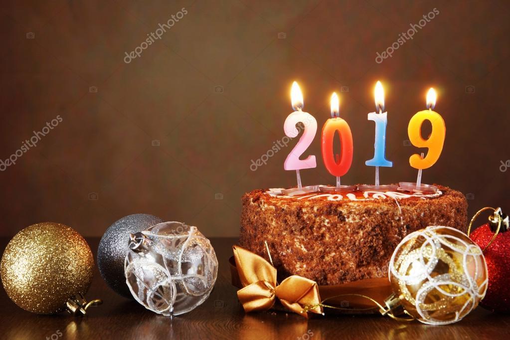 Nouvel an 2019 nature morte. Gâteau au chocolat et boules d\u0027arbre décoratif  avec des bougies allumées sur fond marron \u2014 Image de a,poselenov