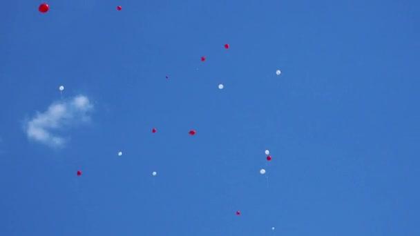 Červené a bílé balónky modré obloze