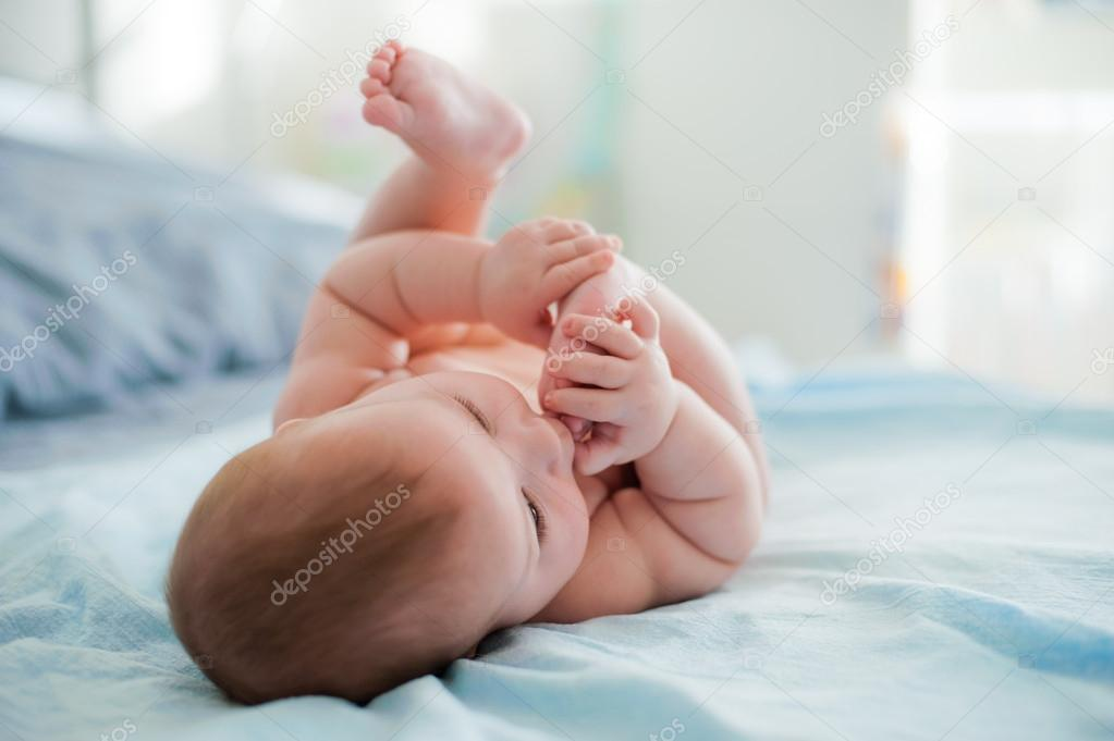 d87776f15 Baby plays with own feet — Stock Photo © Shangarey  62949927