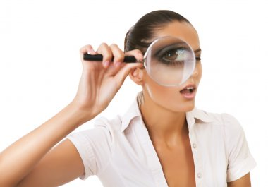 Businesswoman with magnifying glass on eye