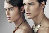 Fotografie pohledný dospělých mužů v náhrdelníky