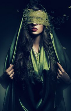 Mysterious woman in green leaves