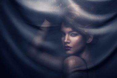 Woman under transparent textile