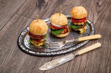 Tasty mini hamburgers on metalic plate