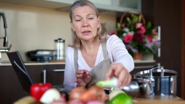Senior woman cooking with help of recipe on laptop.