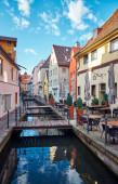 Vertikale Stadtlandschaft. Schmale alte Straße mit Wasserkanal und Restaurant und Café in Memmingen.